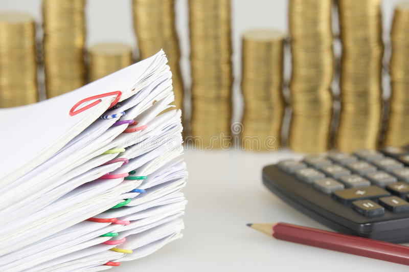 Close up paperwork have blur pile gold coins as background. Close up pile paperwork of report and receipt with colorful paperclip have blur pile of gold coins stock photography