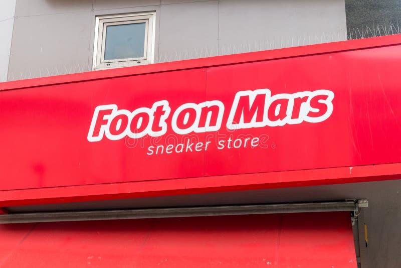 Close-up para o logotipo e o sinal do pé na loja da sapatilha de Marte imagem de stock