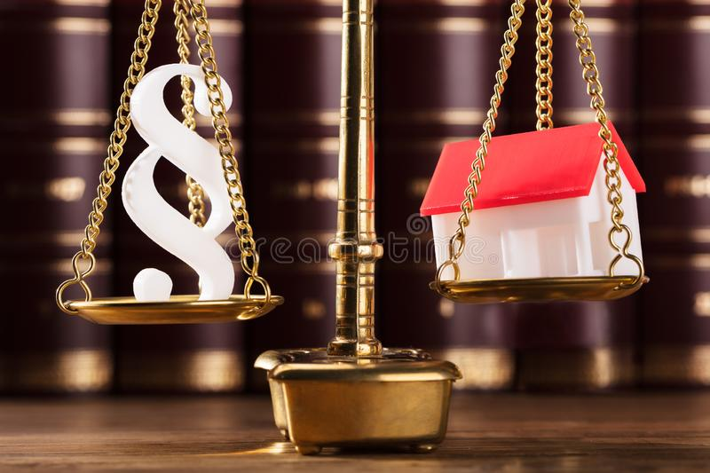 Paragraph Symbol And House Model On Justice Scale. Close-up Of Paragraph Symbol And House Model On Golden Justice Scale stock image