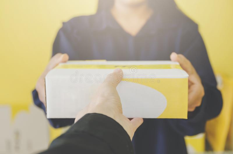 A human hand holding parcel and mailbox for delivery and shipping. Close-up of parcel box and hand holding a package, Delivery concept and shipping of parcel royalty free stock images