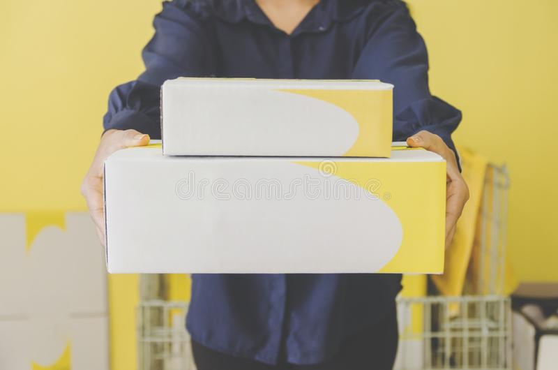 A human hand holding parcel and mailbox for delivery and shipping. Close-up of parcel box and hand holding a package, Delivery concept and shipping of parcel stock image
