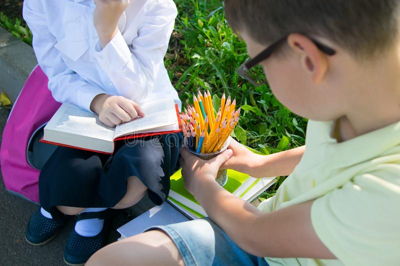 Close-up, in the park, in the fresh air, schoolchildren doing homework, a boy holding a glass with pencils stock photography