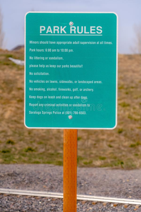 Close up of a Park Rules signage against a rocky and grassy landscape royalty free stock photography