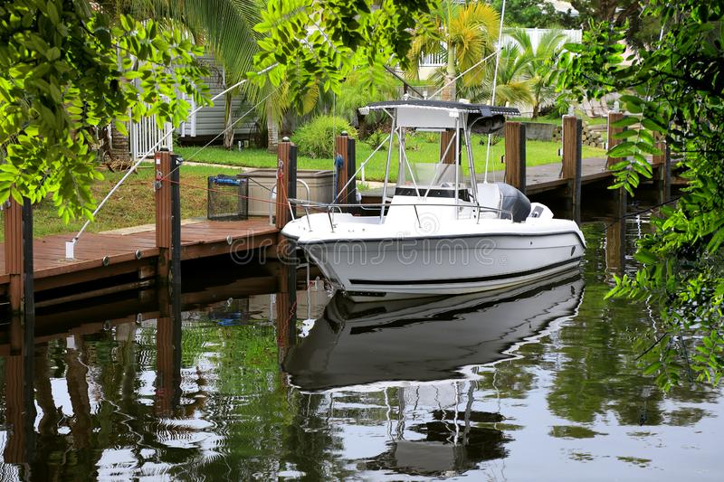 Parked boat at dock on canal in Florida, USA. Close up parked boat at dock on canal in Florida, USA stock photo