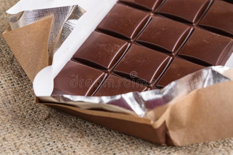 Close-up part of chocolate in opened wrapper on burlap. royalty free stock images