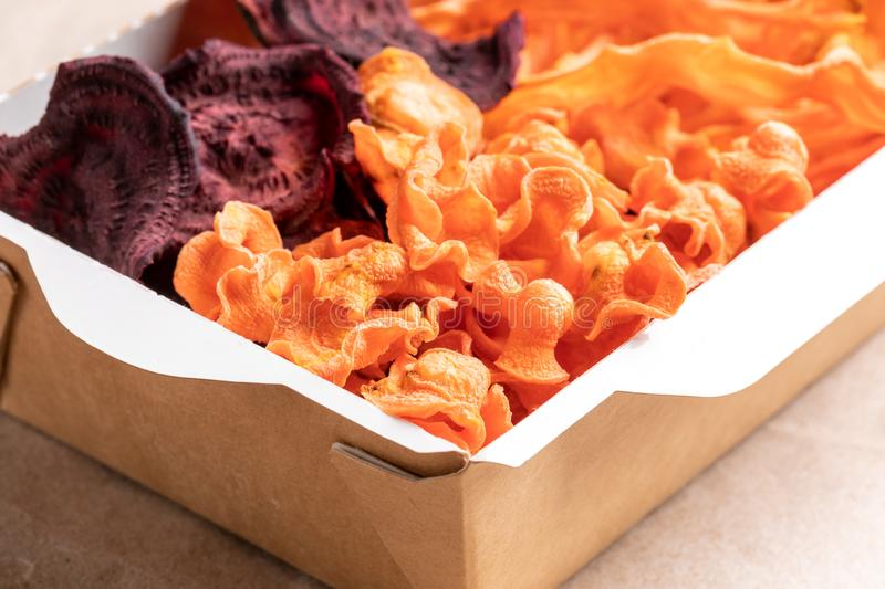 Close-up part of paper box full of healthy vegetable chips. royalty free stock photos