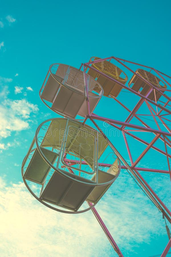 Close up part of pastel ferris wheel on blue sky. Instagram filtered stock photo