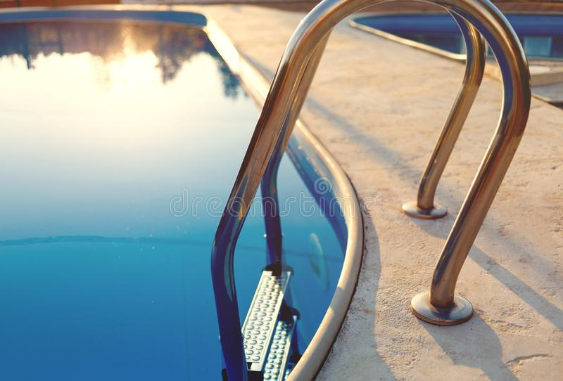 Close-up of a part of swimming pool with a stainless steel ladder and blue water on sunset. Summer vacation, holidays, relax, royalty free stock photo