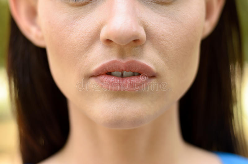 Close up on the parted lips of a thin woman. Close up on the parted lips showing a glimpse of teeth of a thin woman with elfin feature, closeup partial view face royalty free stock photo