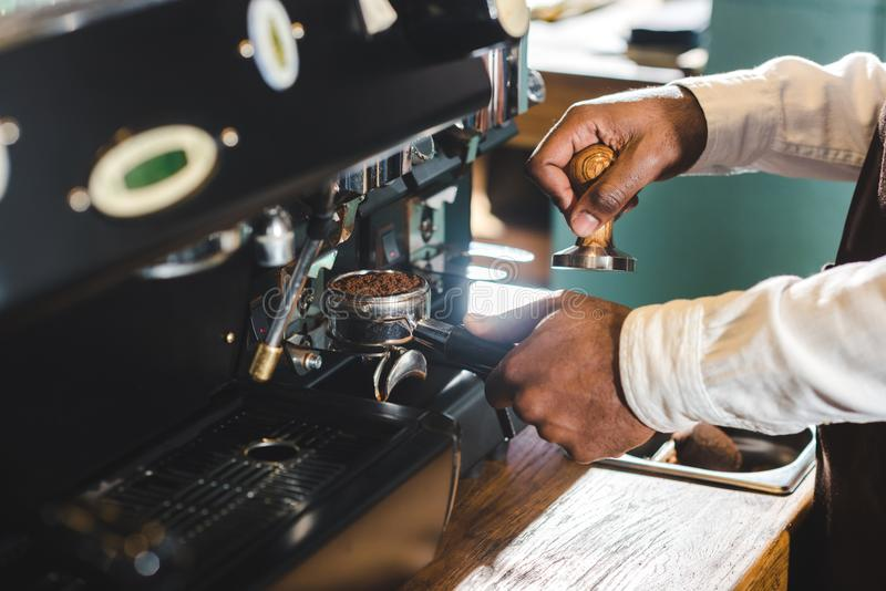 close-up partial view of african american barista in apron making coffee stock photography