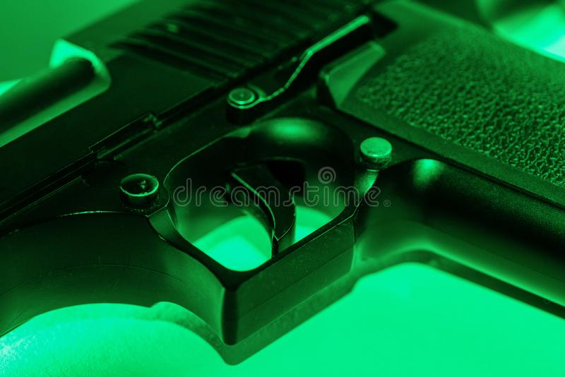 Close up partial view of an automatic hand gun illuminated in green light stock image