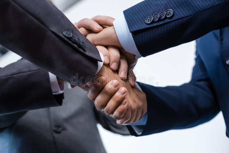 Close-up partial view of businesspeople in formal wear stacking hands together stock photos