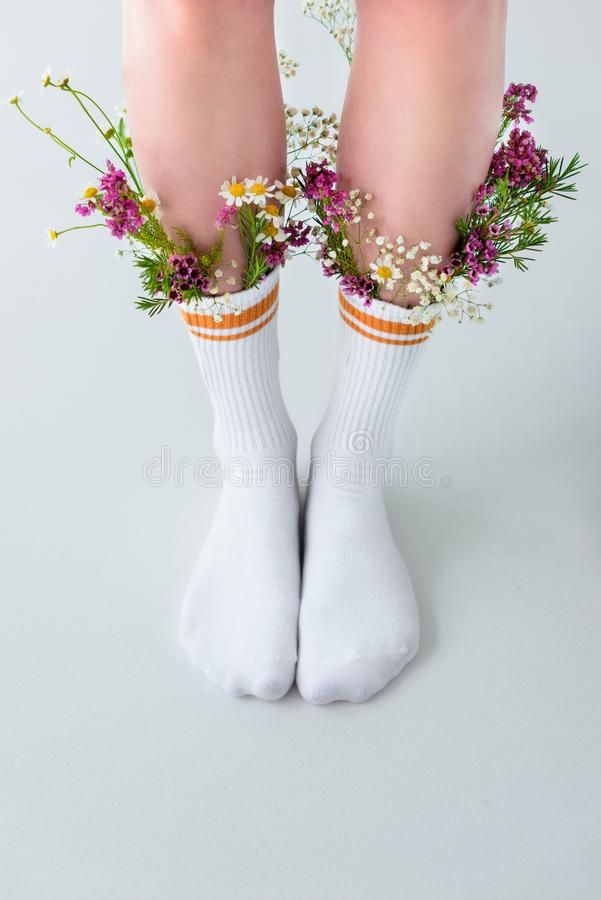 close-up partial view of female legs in socks with beautiful flowers stock photo