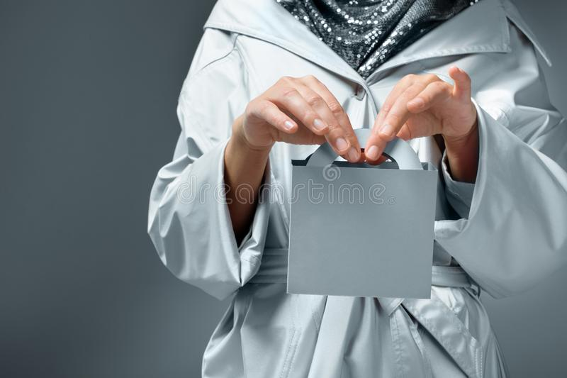 close-up partial view of girl in silver clothes holding small paper bag royalty free stock photos