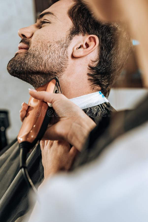 Close-up partial view of hairdresser using electric hair trimmer and cutting beard to client royalty free stock photography