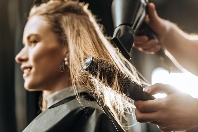 Close-up partial view of hairstylist combing and drying hair to beautiful young woman royalty free stock photography