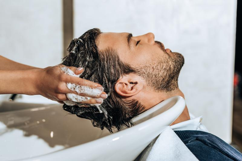 Close-up partial view of hairstylist washing hair to handsome young man royalty free stock photography
