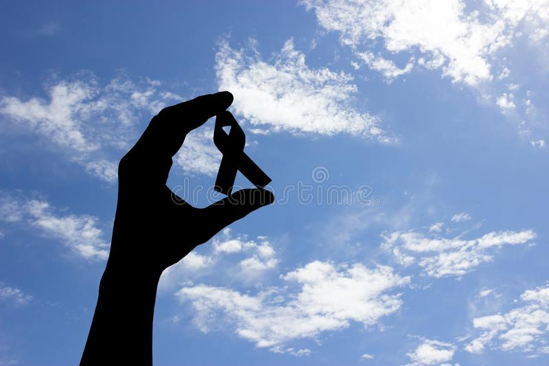 close-up partial view of hand holding cancer awareness ribbon stock photography