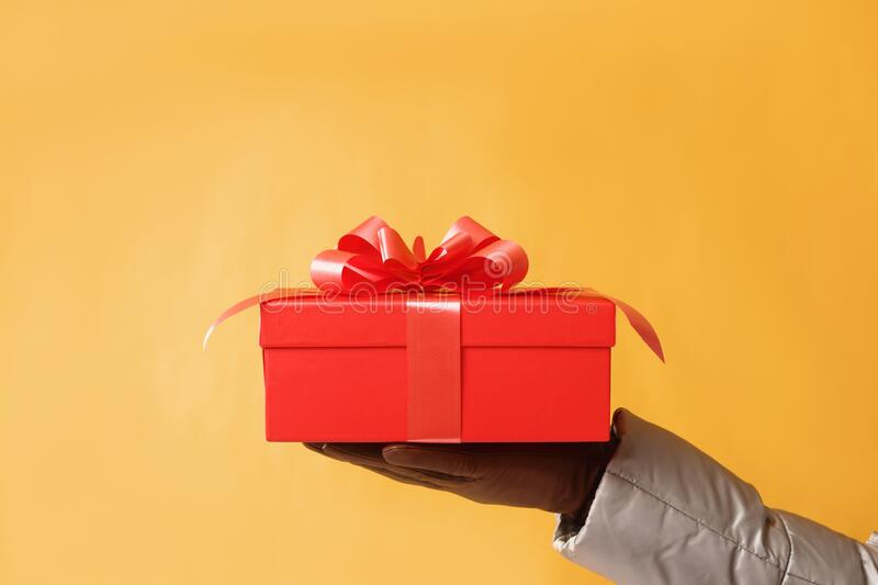 Close-up partial view of man holding red gift box on yellow background.Gift giving concept stock photography