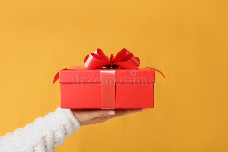 Close-up partial view of man in sweater holding red gift box on yellow background.Gift giving concept stock photo