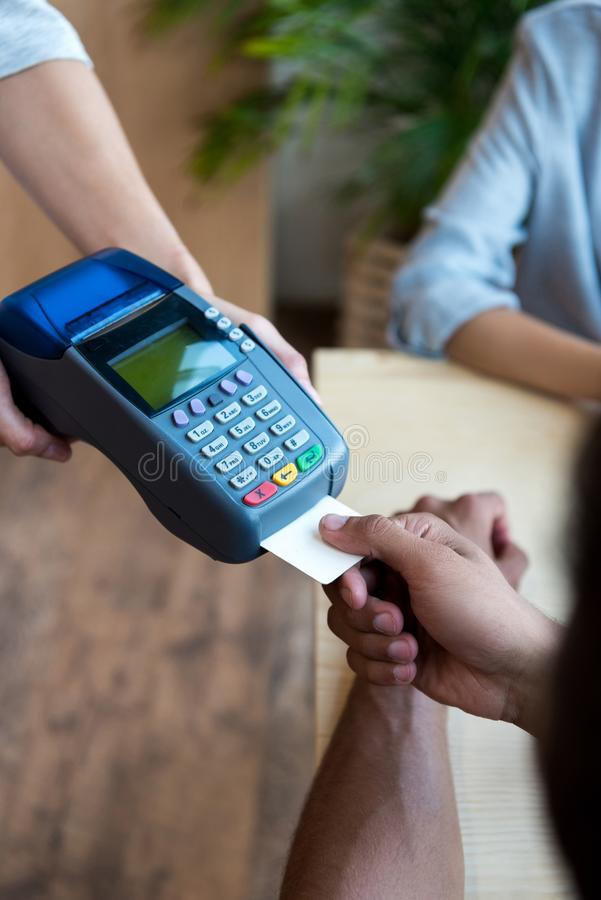 Close-up partial view of payment by credit card and terminal. In cafe royalty free stock image