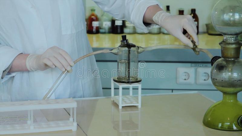 Close-up partial view of scientists making experiment with reagent and flasks. close up of biotechnology research in stock photo