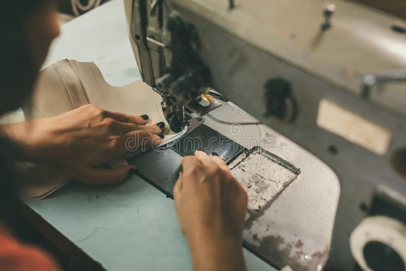 close-up partial view of seamstress working with sewing machine and leather royalty free stock image