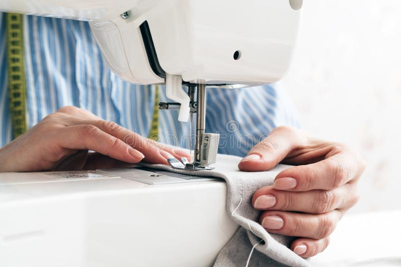 Close-up partial view of seamstress working with sewing machine and textile fabric royalty free stock photo