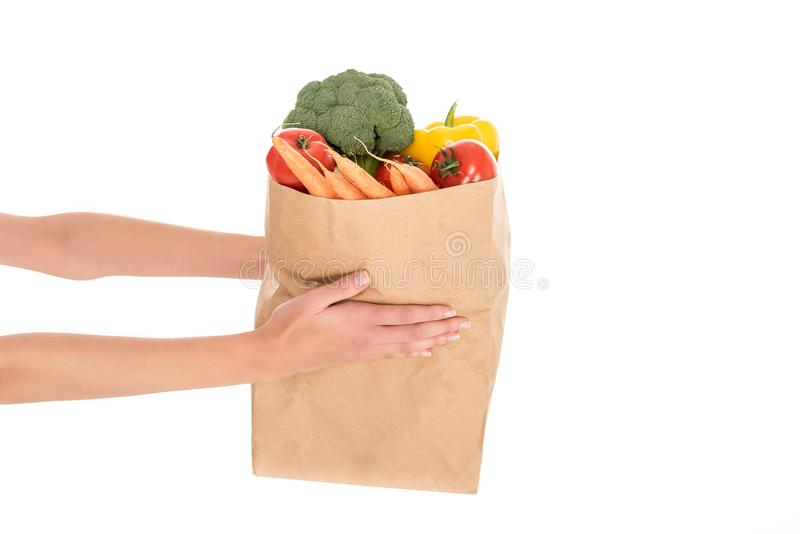 Close-up partial view of woman holding paper bag with fruits and vegetables. Isolated on white stock image