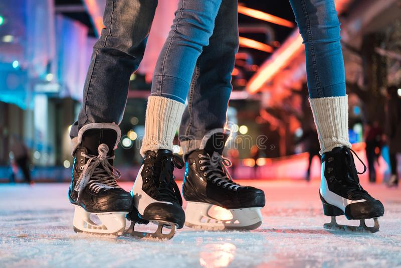 Close-up partial view of young couple in skates ice skating. On rink royalty free stock image