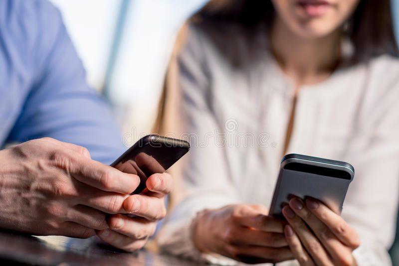 Close-up partial view of young couple using smartphones together royalty free stock images