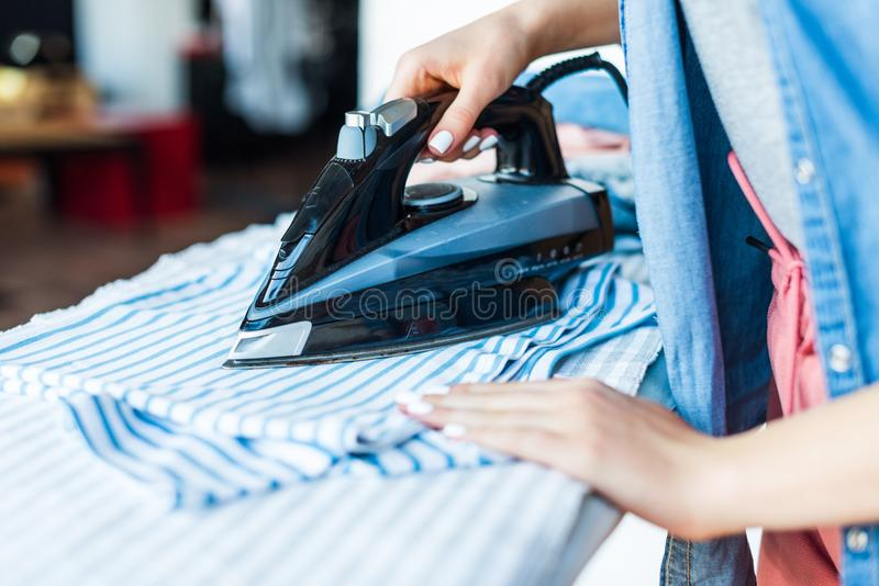 close-up partial view of young woman ironing clothes at home royalty free stock photos