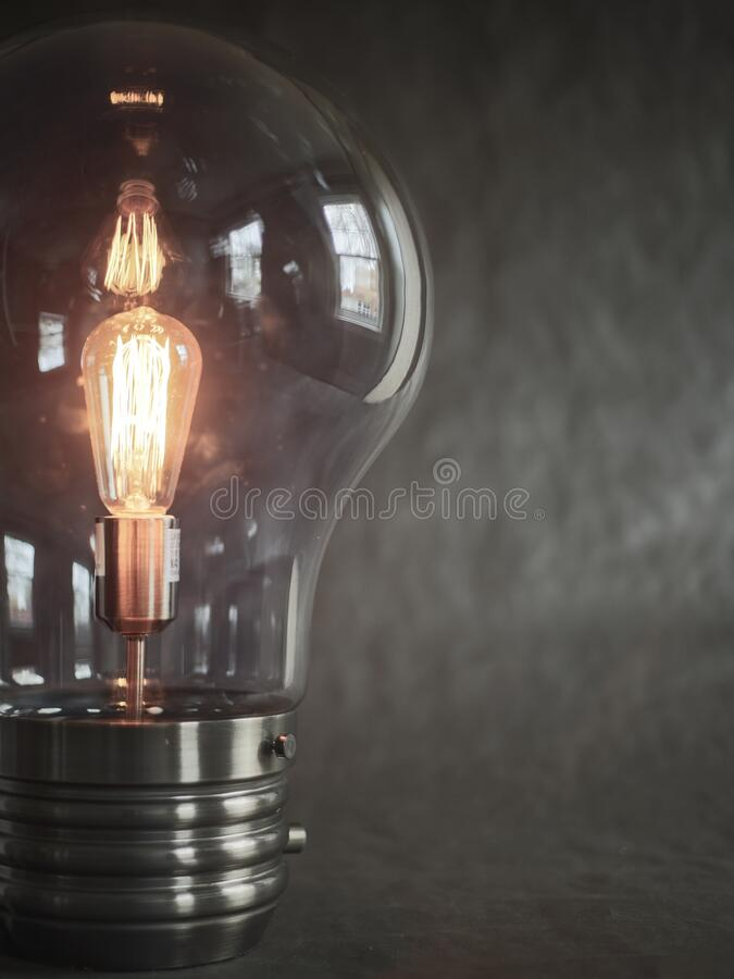 Close Up Partial Viewpoint of Light Bulb/Lightbulb Against a Plain Black Background, Copy/Text Space at Right stock images