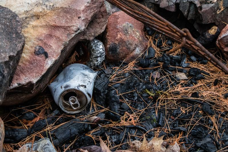 Litter in the fire pit. Close up of a partially burnt can and tinfoil in a fire pit. Don`t litter in the campground. Pack out what you bring in stock photography