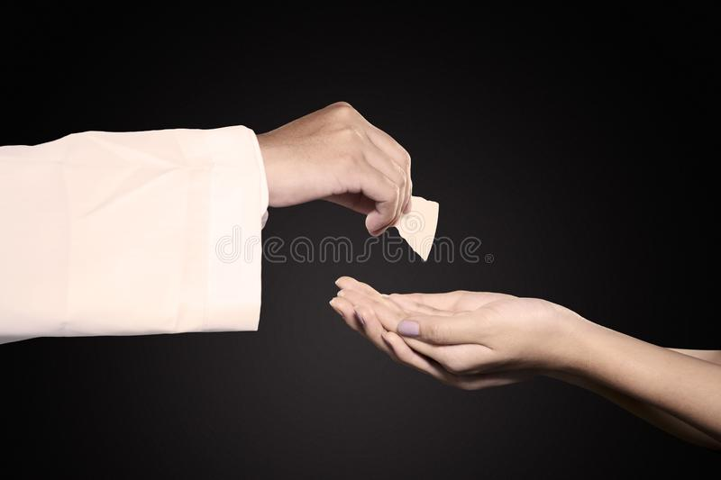 Pastor giving first communion bread to woman. Close up of pastor giving first communion bread on women hands in dark background royalty free stock photo