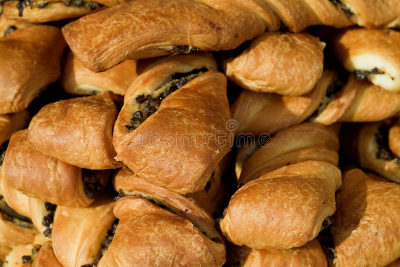 Close-up of pastries. Golden crusted flaky pastries filled with apple and currents royalty free stock images