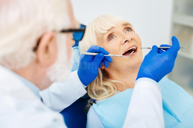 Close up of the patient at the dentists. Taking care about teeth. Close up of peaceful patient sitting in the dental chair while experienced stomatologist curing royalty free stock photo