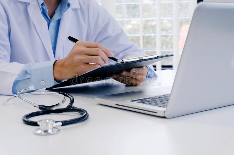close up of patient and doctor taking notes or Professional medical doctor in white uniform gown coat interviewใ stock photography