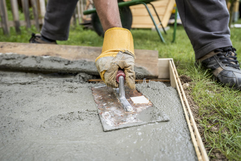 Close up on paver smoothing fresh concrete stock images