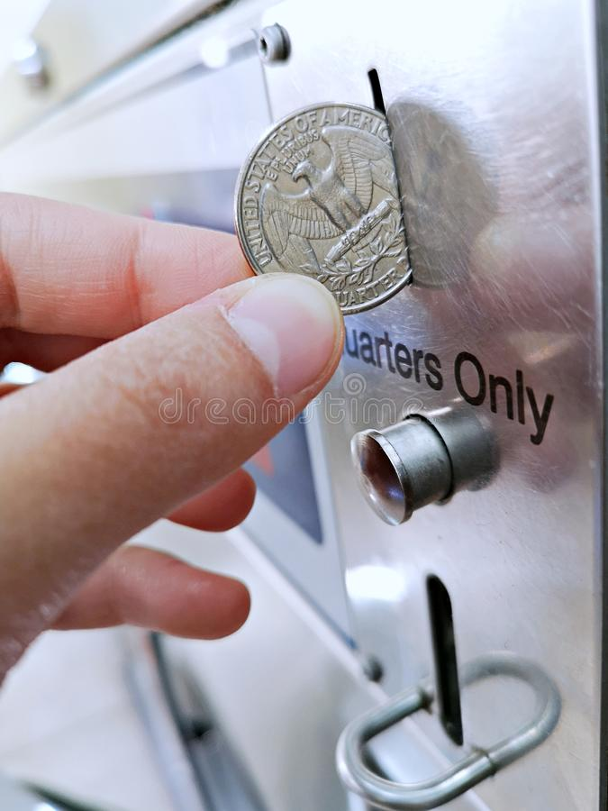 Paying with a quarter coin in a machine. Close-up of paying with a quarter coin in a machine royalty free stock images