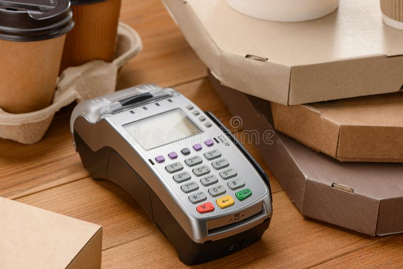 Close-up on a payment terminal. Between pizza boxes and coffee cups. Cashless payment for fast food restaurants stock photos