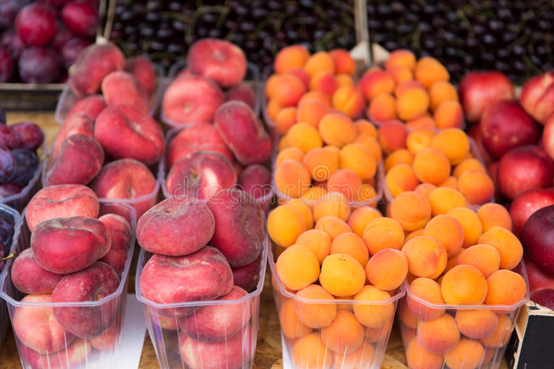 Close up of peaches and apricots at street market. Sale, harvest, food, fruits and agriculture concept - close up of flat peaches and apricots in plastic boxes royalty free stock photography