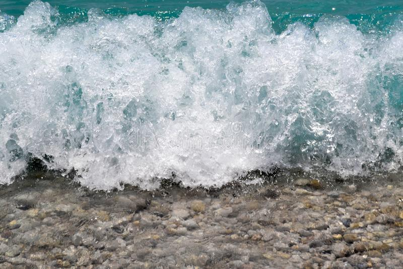 A close-up of pebbles and sea foam. Waves splashing and splattering against the shore, macro shoot stock image