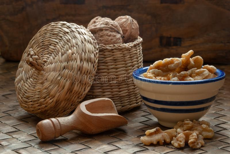 Close-up of peeled and whole walnuts on brown, natural braided background stock photo