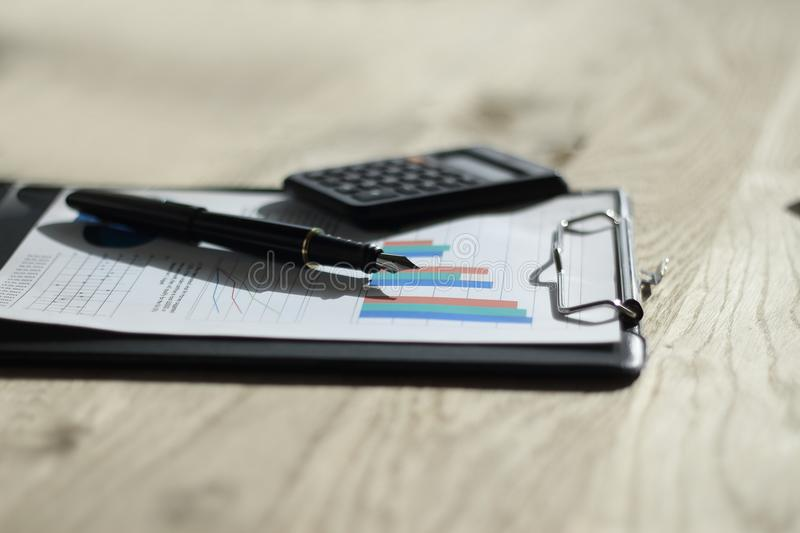 Close up. pen, calculator and clipboard on wooden table. business concept royalty free stock photography