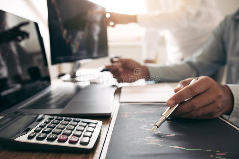 Close up of pen investors are working together with analyzing the stock data graphs in the paper and viewing the data on the stock images