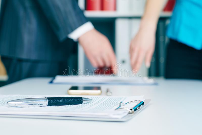 Close-up the pen lies on the documents. Business people hands pointing analyzing at the documents on the background royalty free stock image