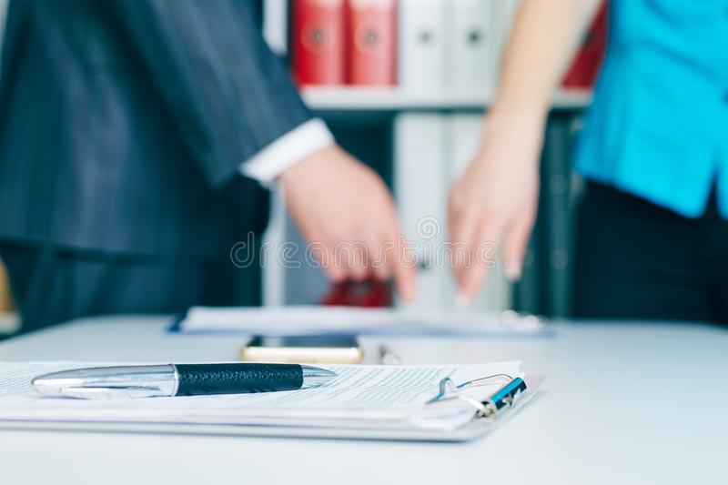 Close-up the pen lies on the documents. Business people hands pointing analyzing at the documents on the background stock image