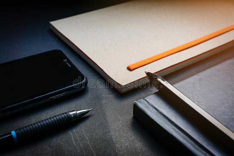 Close up pen placed on black notebook, brown notebook, smartphone and pencil on black desk background in dramatic lighting tone. C royalty free stock photos