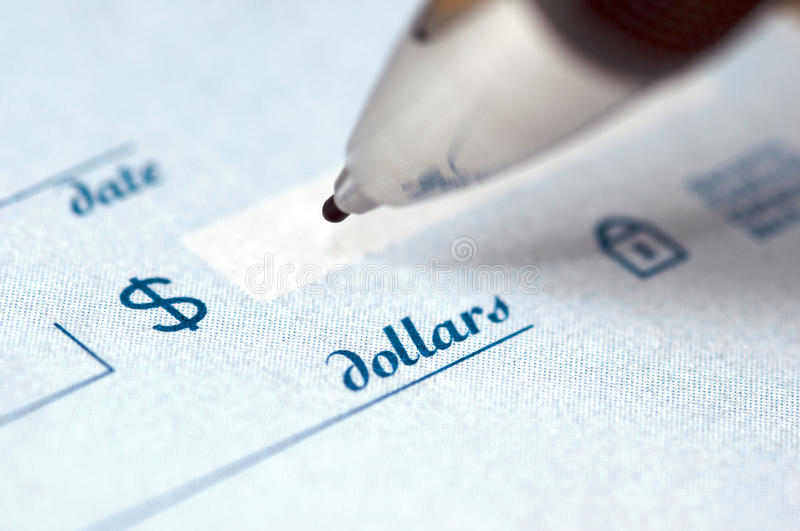 Close up on a pen writing a check stock photo